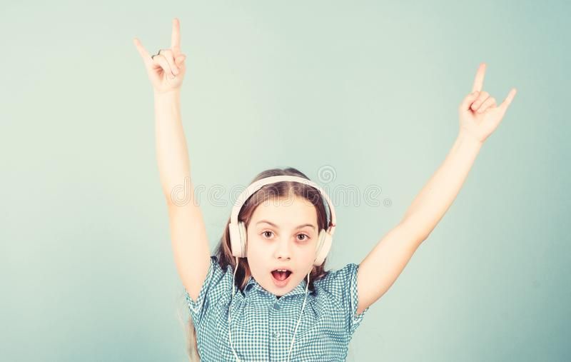 Shes a rock star. Little kid showing horn hand gesture like a hard rock or heavy metal fan. Cute small child listening stock photo