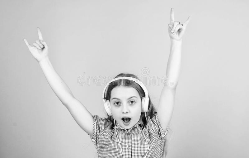 Shes a rock star. Little kid showing horn hand gesture like a hard rock or heavy metal fan. Cute small child listening. To rock music playing in headphones royalty free stock photography