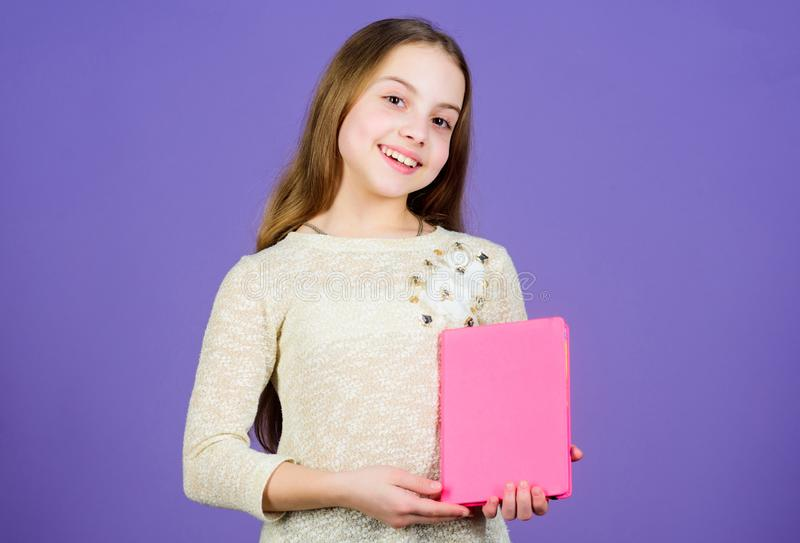 Shes a student of language and literature. Cute little child holding book in English literature. Adorable small girl stock photos