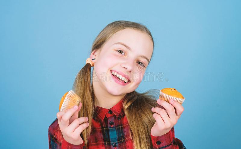 Shes so sweet that makes the food taste good. Small girl smiling with freshly baked dessert food. Happy little child stock photography