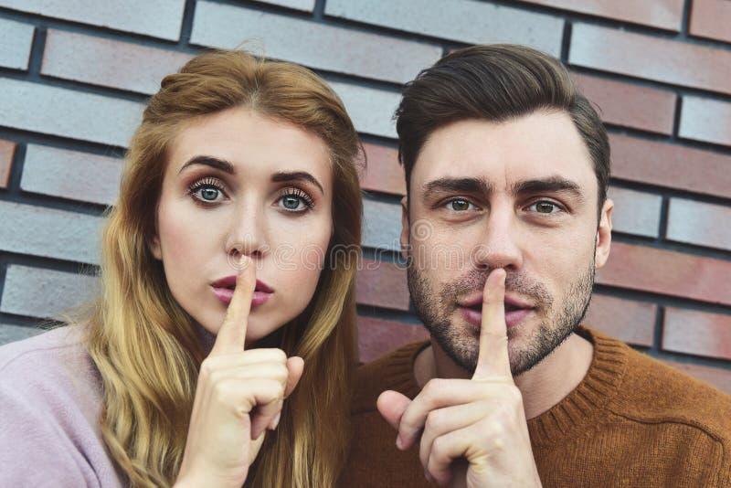 Shh, не скажите к кто-нибудь эту частную информацию Удивленные кавказские пары сделать для того чтобы shush жест с удивленными вы стоковая фотография