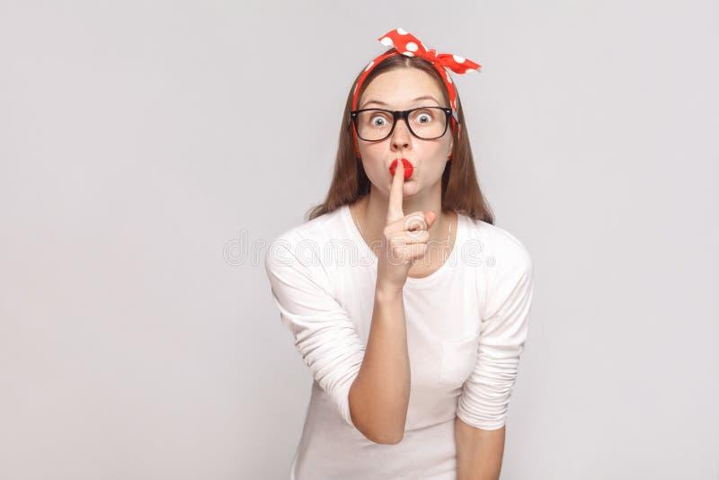 Shh! detta är hemligt stående av den härliga emotionella unga kvinnan arkivfoton