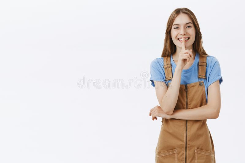 Shh girl wants share secret. Portrait of charming friendly-looking pretty woman in brown dungarees and blue t-shirt stock photography