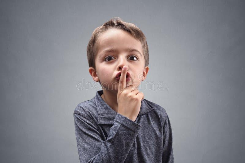 Shh Junge mit dem Finger auf Lippen stockbilder