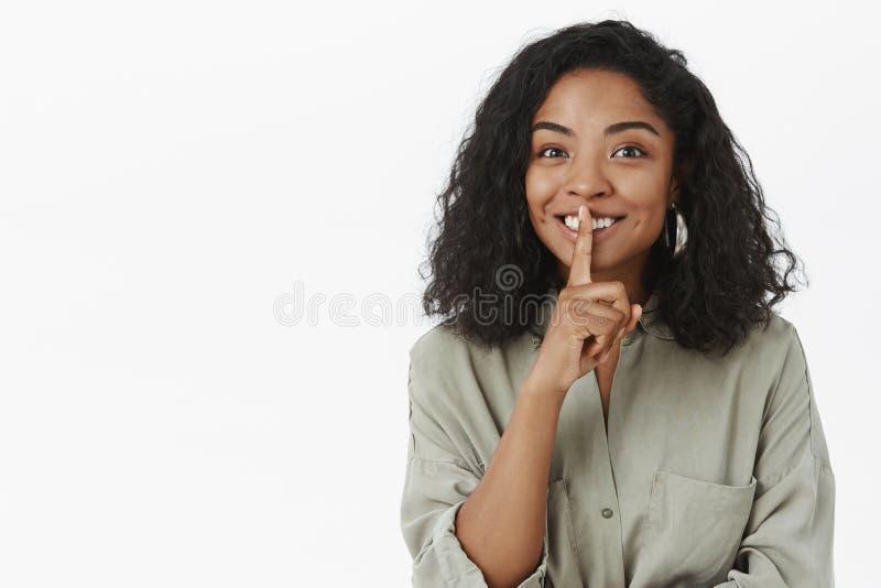 Shh kan u geheimen houden Portret van charmeren vriendschappelijk-kijkt opgetogen leuke donker-gevilde vrouw met krullend kapsel stock fotografie