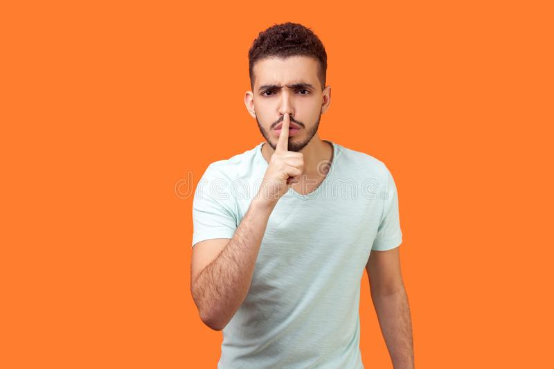 Shh, make silence please! Portrait of serious brunette man showing quiet gesture. isolated on orange background. Shh, make silence please! Portrait of serious royalty free stock photos