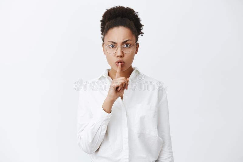 Shh, quiet, silence in class. Strict and serious-looking dark-skinned female teacher in white-collar shirt and glasses stock images