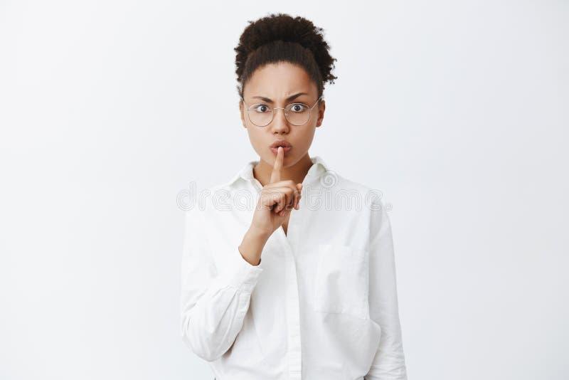 Shh, ruhig, Ruhe in der Klasse Strenger und ernst-aussehender dunkelhäutiger weiblicher Lehrer im Bürohemd und in den Gläsern stockbilder