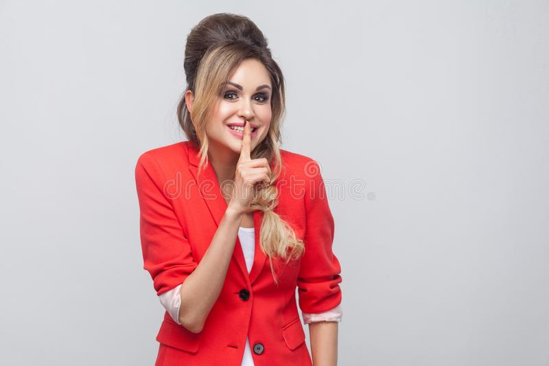 Shh, this is secret between us. Portrait of funny beautiful business lady with hairstyle and makeup in red fancy blazer, standing. And looking at camera with stock photos