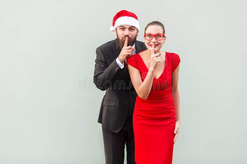 Shh sign. Big secret, shut up! Well dressed businessman and woman looking at camera and showing quiet sign. Shh sign. Big secret, shut up! Well dressed stock photos