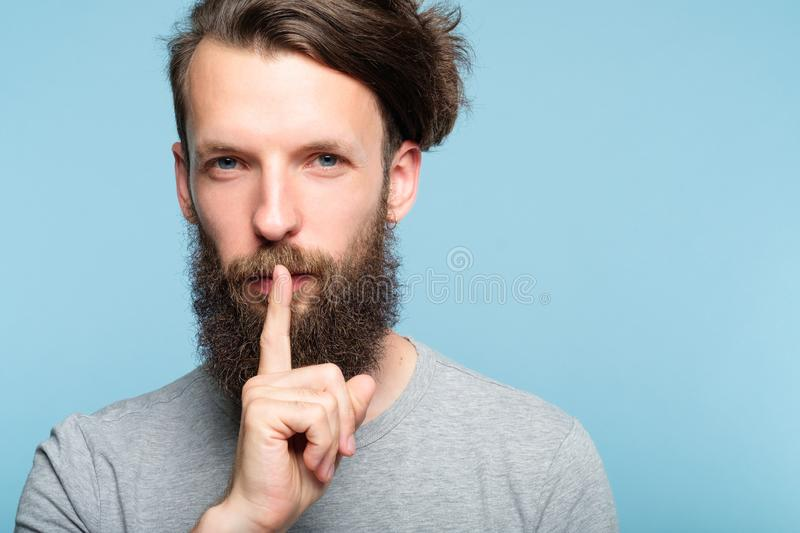 Shh silence quiet man showing finger lips gesture stock images