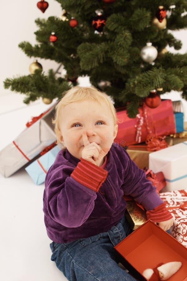 Shhh - bebé lindo que abre disimuladamente los regalos de la Navidad fotografía de archivo libre de regalías