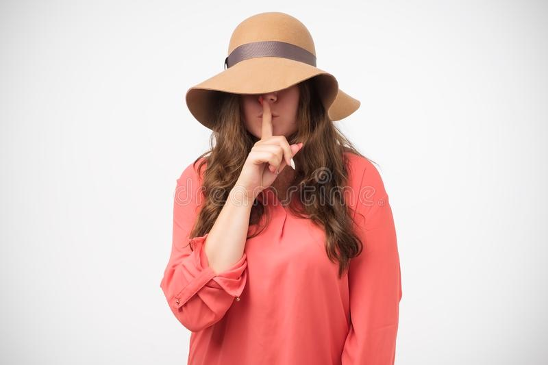 Shhh concept. Portrait of mysterious girl in hat gesture silence sign holding forefinger on lips. Hiding from problems stock image