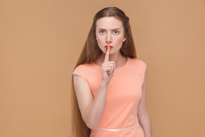 Shhh podpisuje, poważna kobieta dotyka jej wargi z palcem fotografia royalty free