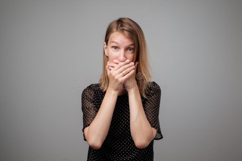 Shhhh? Mantenha o silêncio Boca europeia assustado da coberta da mulher com mãos ao levantar à câmera no fundo cinzento do estúdi imagem de stock