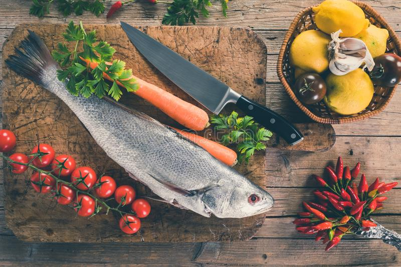 Shi Drum Fish Cooking. Shi drum fish Umbrina cirrosa on old wooden board with carrot, cherry tomatoes, black tomatoes, lemon, garlic, parsley and chili peppers royalty free stock image