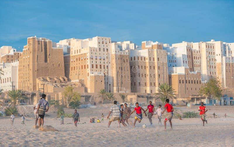 SHIBAM, YÉMEN - février, 21 : Garçons yéménites jouant le football images stock