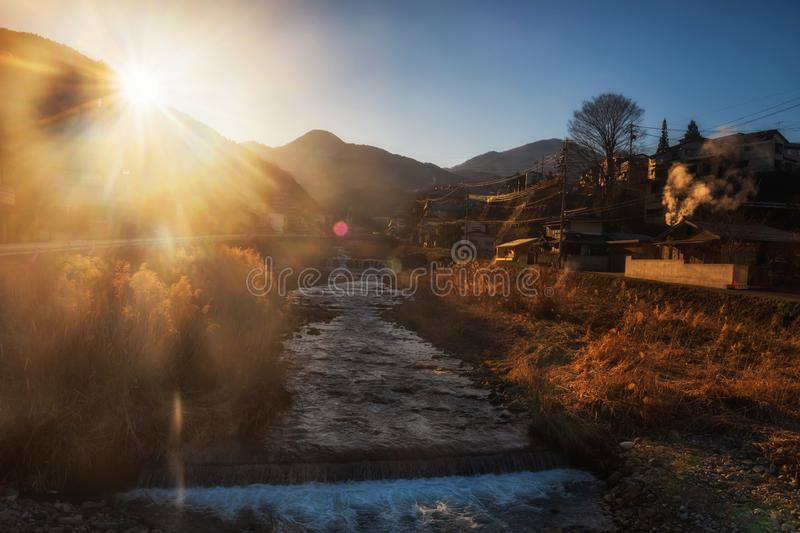 Shibu onsen cityscape at sunrise. Shibu onsen cityscape or landscape with flowing water river at sunrise, Yamanouchi, Nagano, Japan. The town is famous for hot royalty free stock photography