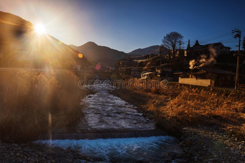 Shibu onsen town at sunrise, Yamanouchi. Shibu onsen town and cascade river at sunrise with flare light, Yamanouchi, Nagano, Japan. The town is famous for hot royalty free stock photography