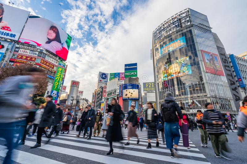 Shibuya, Tóquio, Japão - 26 de dezembro de 2018: Povos dos pedestres da multidão que andam na faixa de travessia da zebra no dist fotos de stock royalty free
