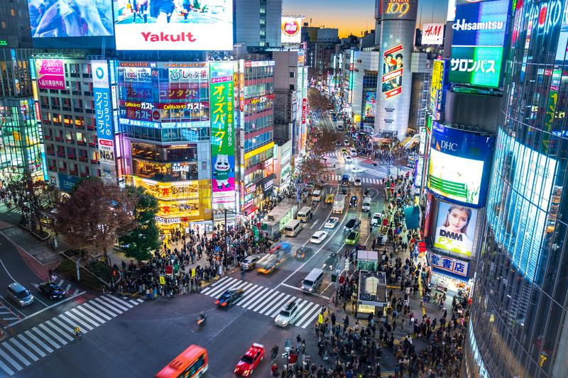 Shibuya, Tokyo, Japan - December 24, 2018: Top view of vehicles drive pass Shibuya district with people waiting to walk on zebra. Crosswalk at night in Tokyo stock photography