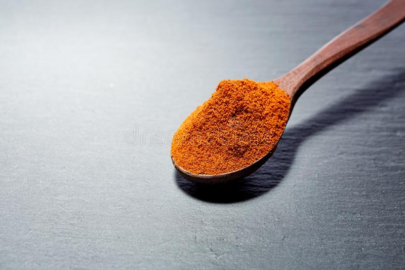 Shichimi pepper in Wooden spoon on black plate, royalty free stock photo