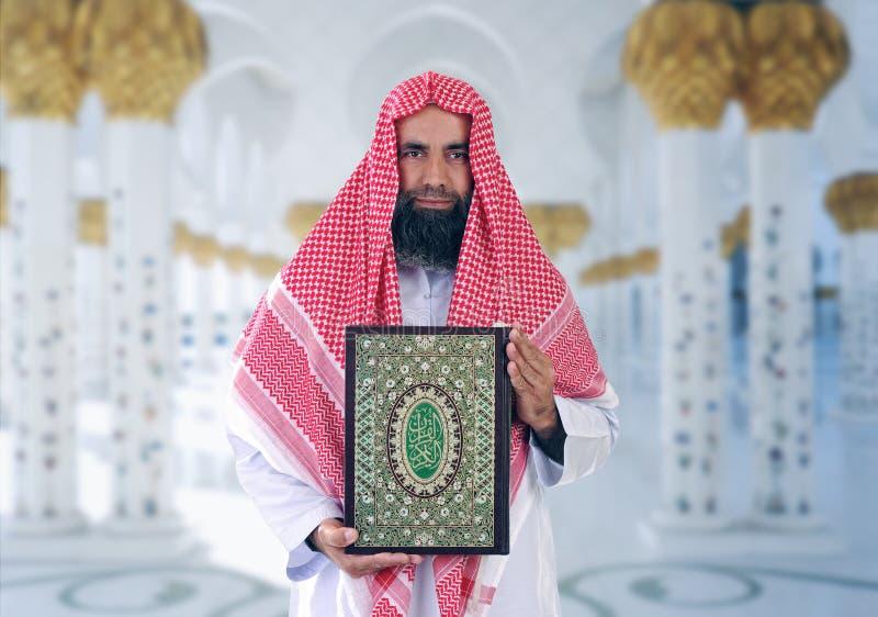 Shiekh arabo islamico che presenta Quran fotografie stock