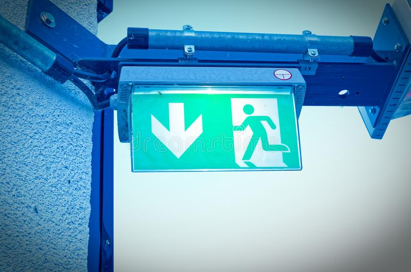 Shield with emergency exit and exit symbol in blue optics. In green royalty free stock image