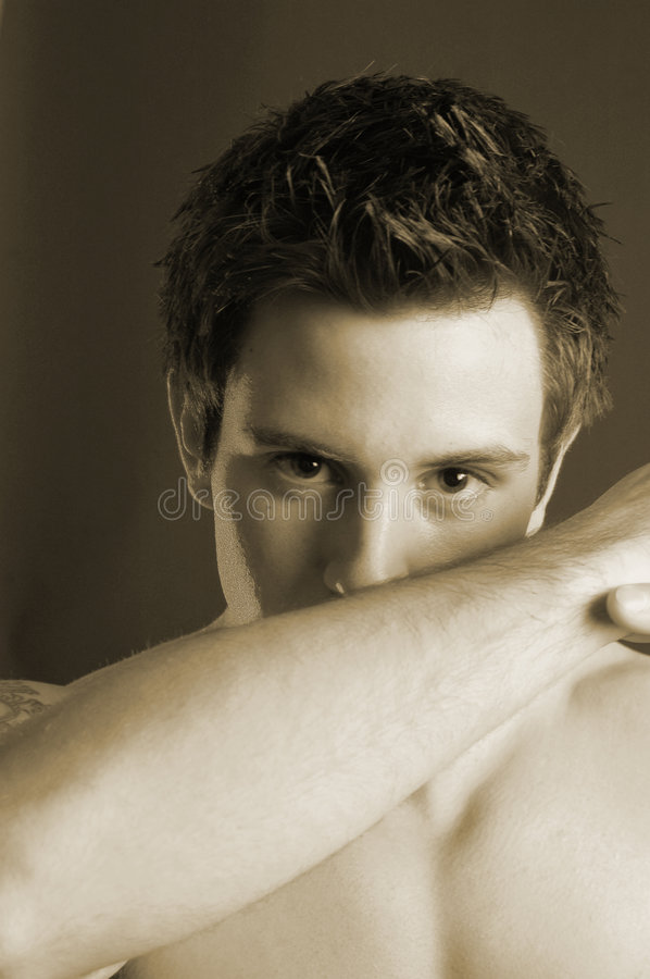 Shifty male sepia. Sneaky male model . male is young and has spikey hair. peering over his forearm royalty free stock photos