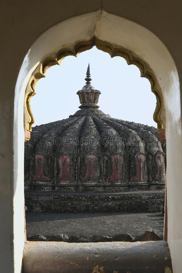 Shikhara carved in Stone masonry over Mandapam as seen from arched opening of balcony over main Gateway at Vitthal Temple, Palashi stock photo