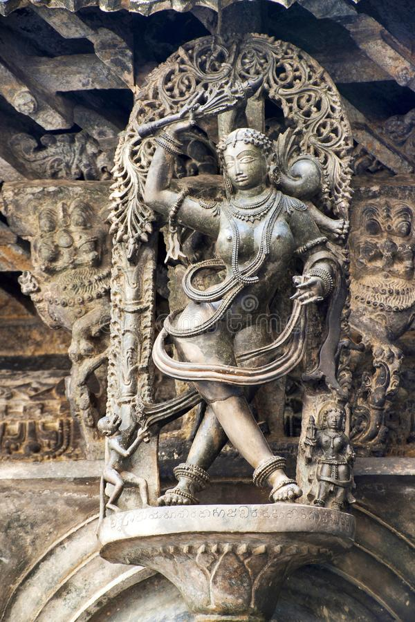 Shilabalika, celestial maiden, as a Kapikupite. Monkey, in the bottom left corner, pulling Saree. Chennakeshava temple, Belur, Kar. Nataka India Notice the royalty free stock photo