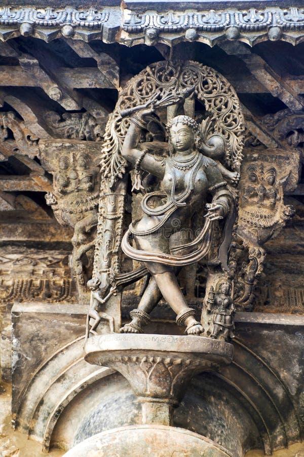 Shilabalika, donzela celestial, como um Kapikupite Monkey, no canto de inferior esquerdo, puxando o Saree Templo de Chennakeshava fotos de stock