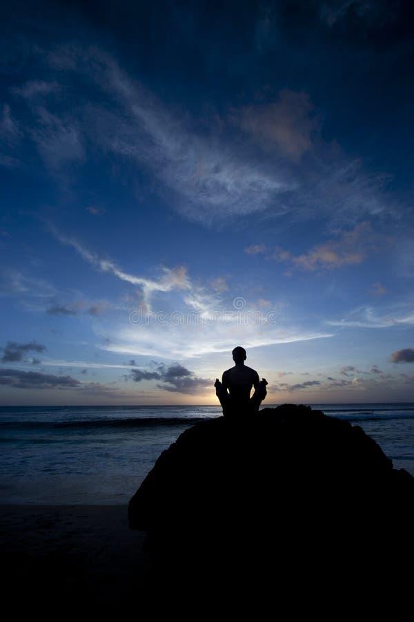 Shilouette do homem que meditating na praia fotos de stock royalty free