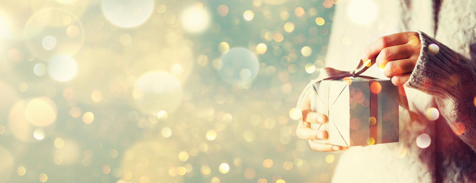 Shimmer background with snow, light bokeh. Woman hands opening gift box. Christmas, new year, birthday concept. Banner, copy space royalty free stock photo