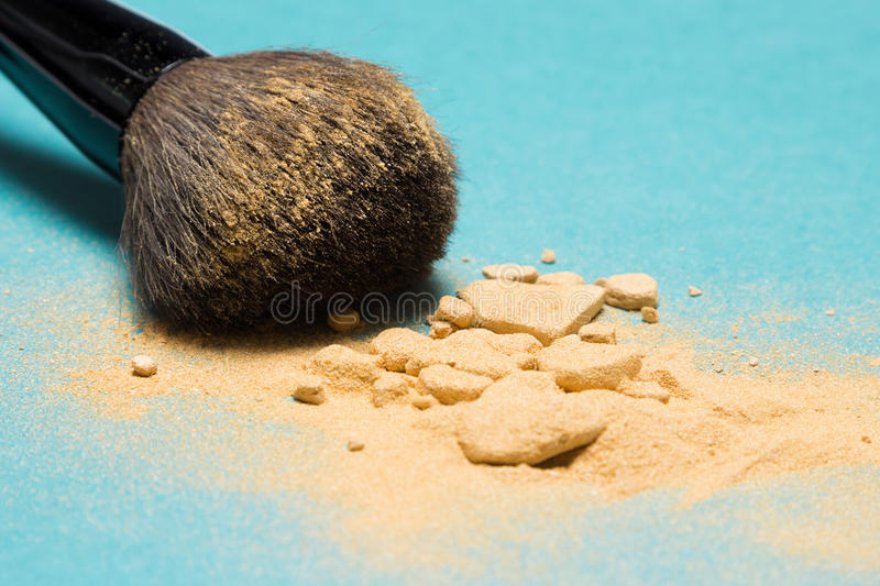 Shimmer powder golden color with makeup brush. Close-up of crushed mineral shimmer powder golden color with makeup brush on blue background. Very shallow depth stock photography