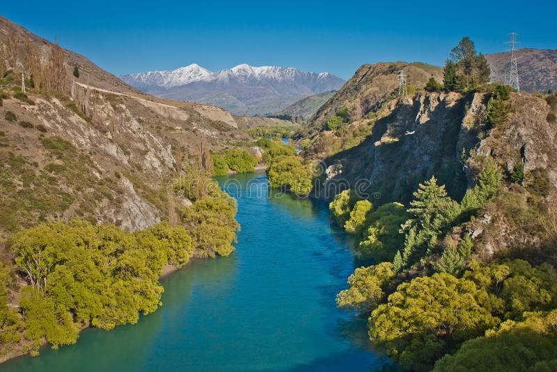 Shimmering blue water of Kawarau river near Queenstown, New Zealand. Shimmering blue water of Kawarau river, dream traveling in New Zealand, the best world royalty free stock photo