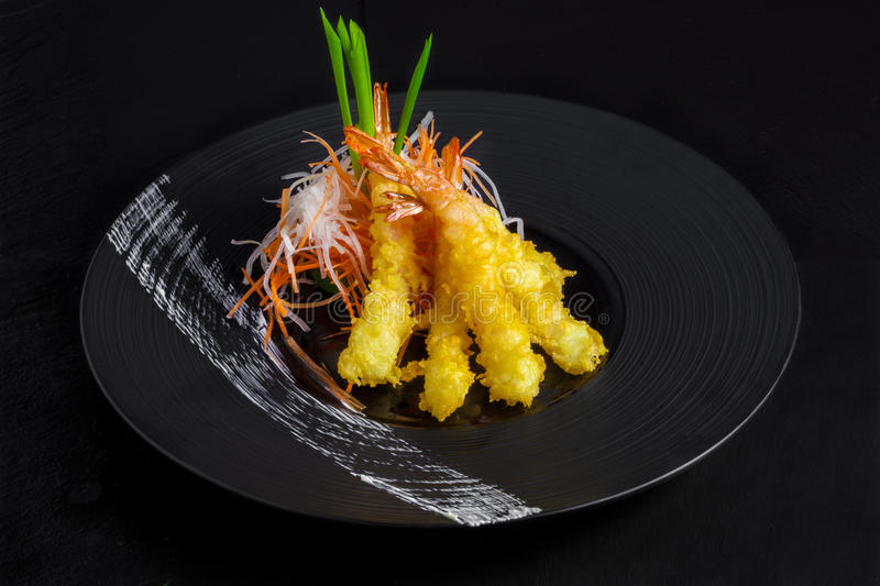 Shimps in fried tempura on black stock image