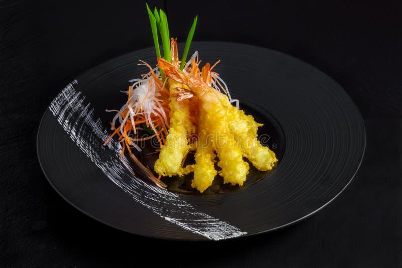 Shimps in gebraden tempura op zwarte stock afbeelding