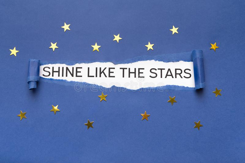 Shine like the stars bursting out from torn blue paper. Inspirational phrase Shine like the stars appearing behind torn blue paper with small golden stars royalty free stock photos