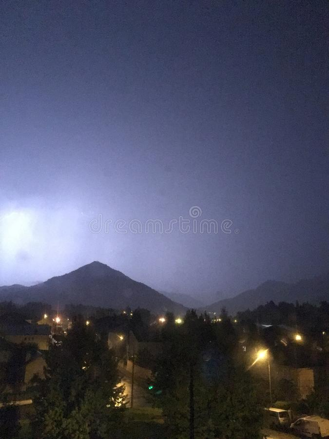 Shine and thunderstorm above mountain and city stock image