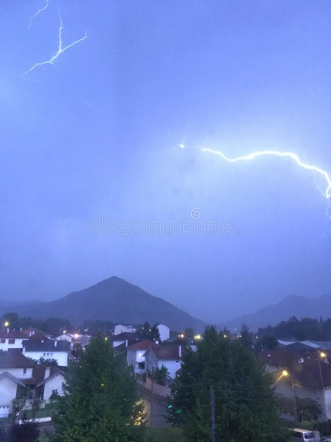 Shine and thunderstorm above mountain and city stock photo