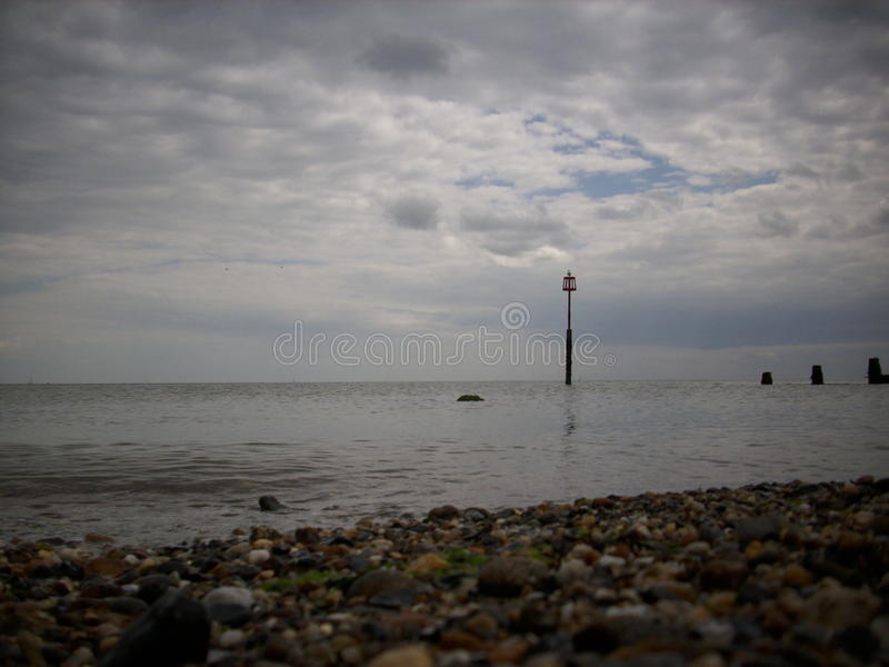 Beach, sea and breakwater. Shingle beach with calm sea and breakwater dipping down into the sea. Low level view. Marker post with seagull just completes the stock photography