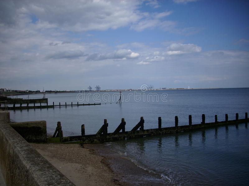 Beach, breakwaters and sea. Shingle beach with sea wall, calm sea and breakwaters (groynes) dipping down into the sea. Distant view of docks. Lovely blue sky as royalty free stock photos
