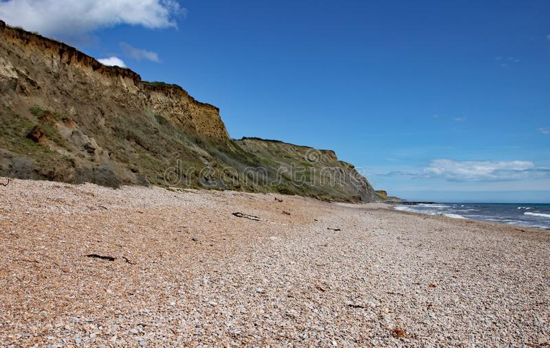 The shingle beach at Eype in Dorset on a sunny day, The sandstone cliffs of the Jurassic coast can be seen in the background.  stock photos