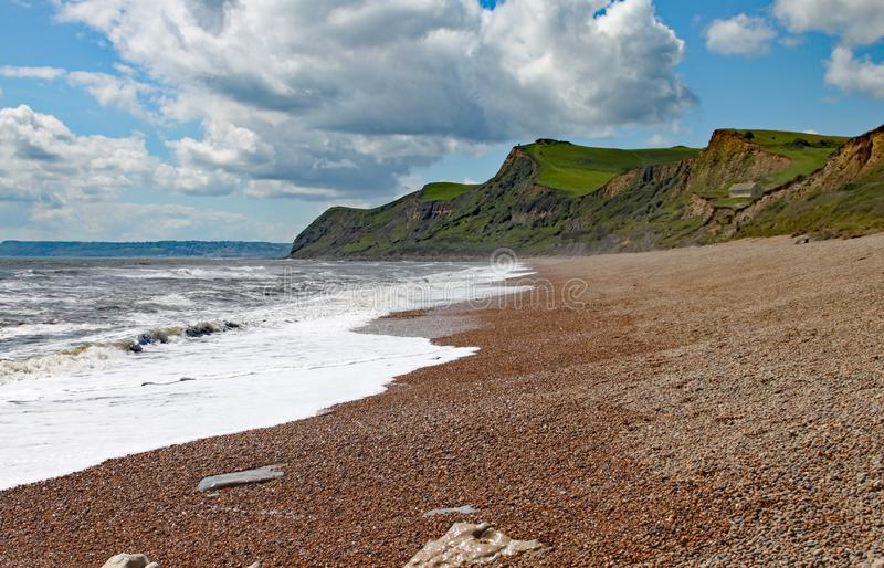 The shingle beach at Eype in Dorset on a sunny day, The sandstone cliffs of the Jurassic coast can be seen in the background.  stock image