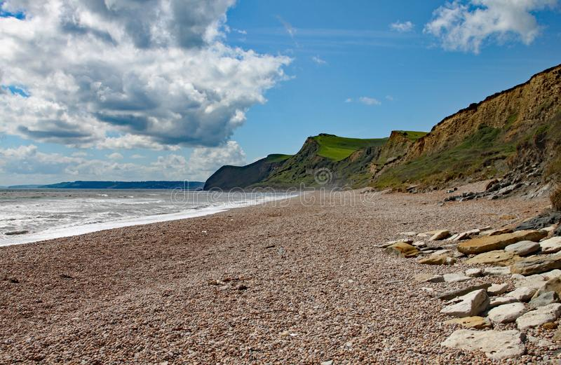 The shingle beach at Eype in Dorset on a sunny day, The sandstone cliffs of the Jurassic coast can be seen in the background.  royalty free stock photos