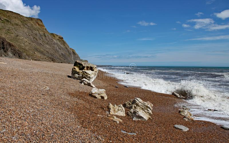 The shingle beach at Eype in Dorset on a sunny day, The sandstone cliffs of the Jurassic coast can be seen in the background.  royalty free stock images