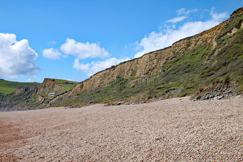 The shingle beach at Eype in Dorset on a sunny day, The sandstone cliffs of the Jurassic coast can be seen in the background.  stock images