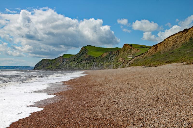 The shingle beach at Eype in Dorset on a sunny day, The sandstone cliffs of the Jurassic coast can be seen in the background.  stock photo