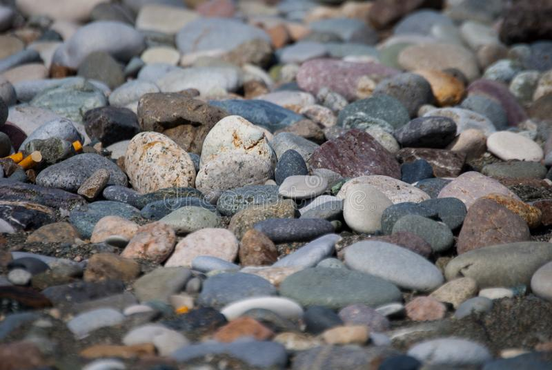 A shingle beach or beach stone. Shingle beaches are typically steep, because the waves easily flow through the coarse, porous surface of the beach, decreasing stock photography